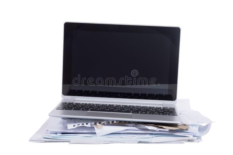 不整洁堆与一台开放膝上型计算机的文书工作 免版税库存照片
