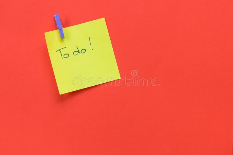 与'要做的'文本的黄色备忘录隔绝在红色背景 免版税库存图片