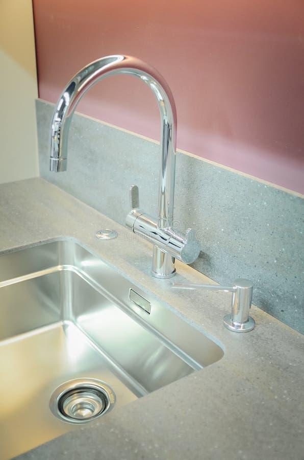 与一个人为石工作台面的一个新的厨房水槽 现代厨房内部的概念 垂直的摄影 免版税库存图片