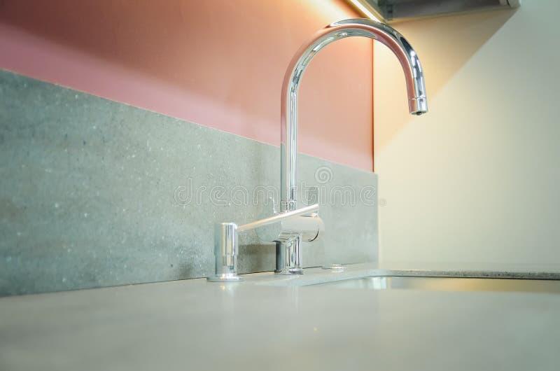 与一个人为石工作台面的一个新的厨房水槽 现代厨房内部的概念 库存照片