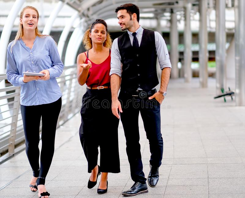 与一个人的企业队和两名妇女走并且谈论关于他们的工作在白天在街道 免版税库存图片