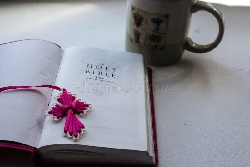 与一个十字架的一部开放圣经与一杯茶在白色背景的 免版税库存图片