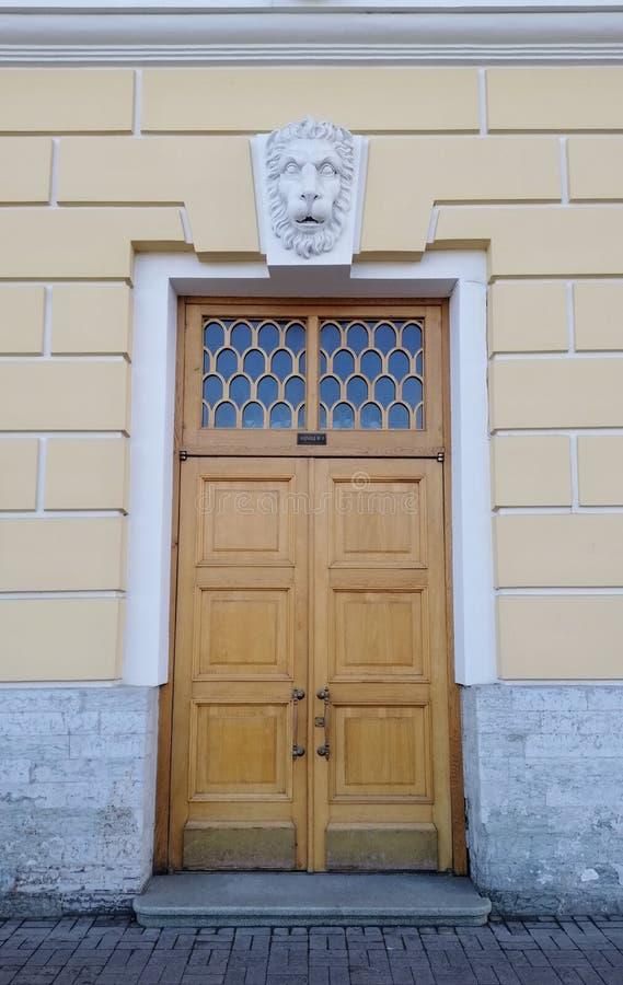 与一个古老大厦的狮子的头的浅浮雕的门 免版税图库摄影