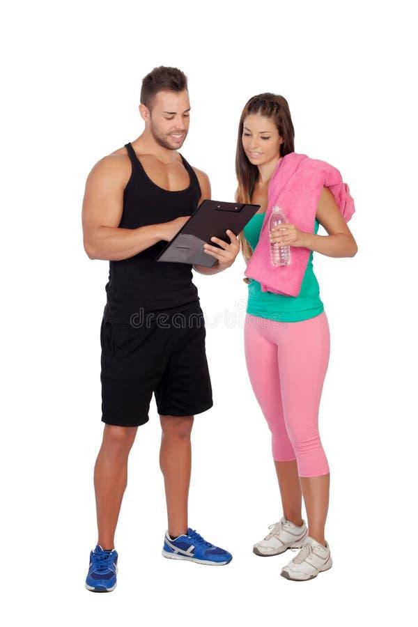 与一个可爱的女孩的英俊的个人教练员 免版税库存照片