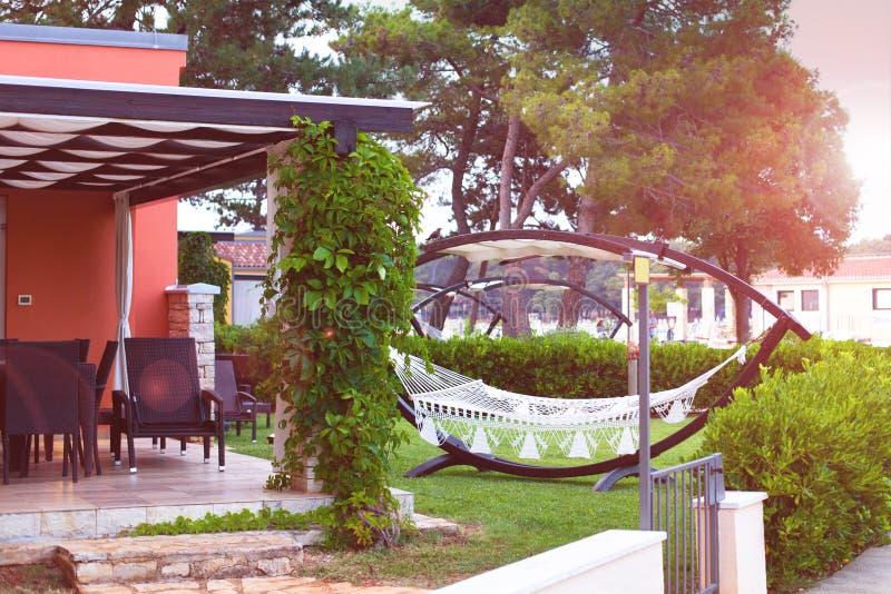 与一个吊床的松弛时间在夏天庭院里在一家豪华旅馆里 暑假、旅行和休闲 库存照片