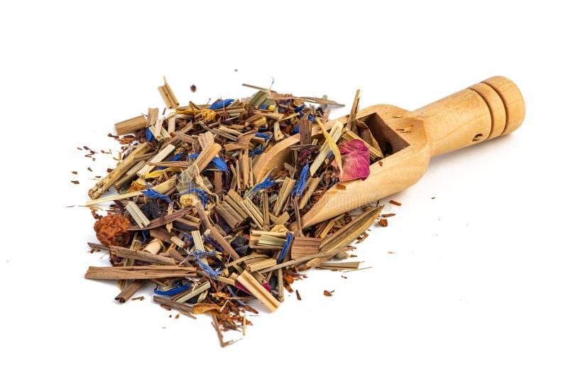 与一个土气木瓢的清凉茶堆在白色背景 薄菏,柠檬香茅,矢车菊,玫瑰花瓣 免版税库存照片