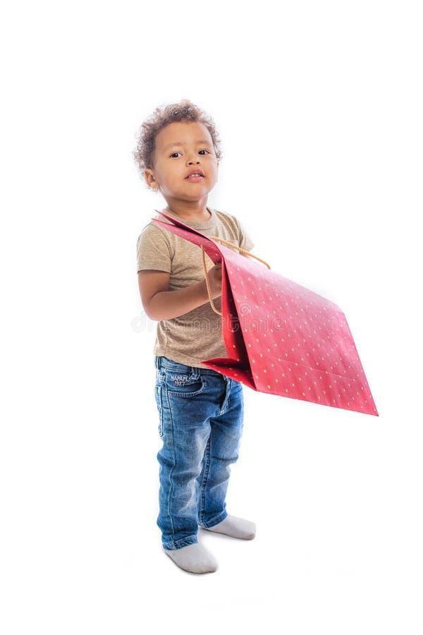 与一个大包裹的照相机的深色皮肤的童颜与一件礼物的在被隔绝的背景 库存照片