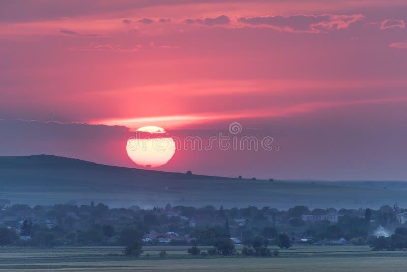 与一个大落日的美好的农村风景 免版税库存照片