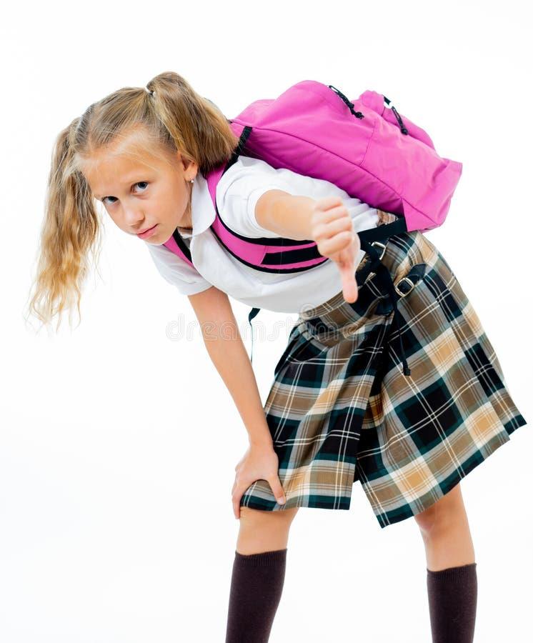 与一个大重的书包的年轻疲乏和哀伤的逗人喜爱的学校女孩身分在她在后面的孤立白色背景 免版税库存照片