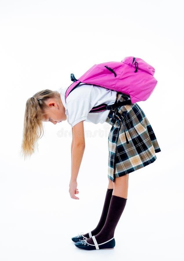 与一个大重的书包的年轻疲乏和哀伤的逗人喜爱的学校女孩身分在她在后面的孤立白色背景 库存照片
