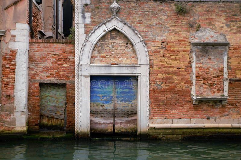 与一个威尼斯式大厦的木门的被成拱形的入口在运河的,威尼斯 图库摄影