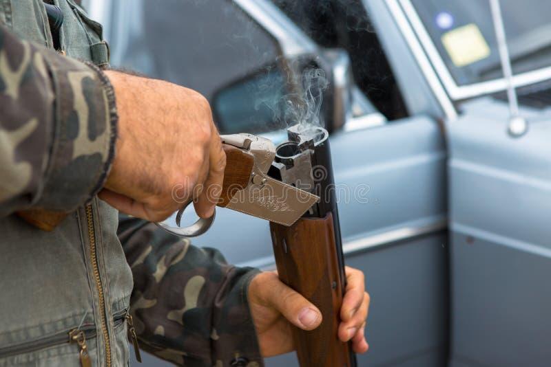 与一个帽子和一杆枪的猎人寻找在干草原的牺牲者 免版税库存照片