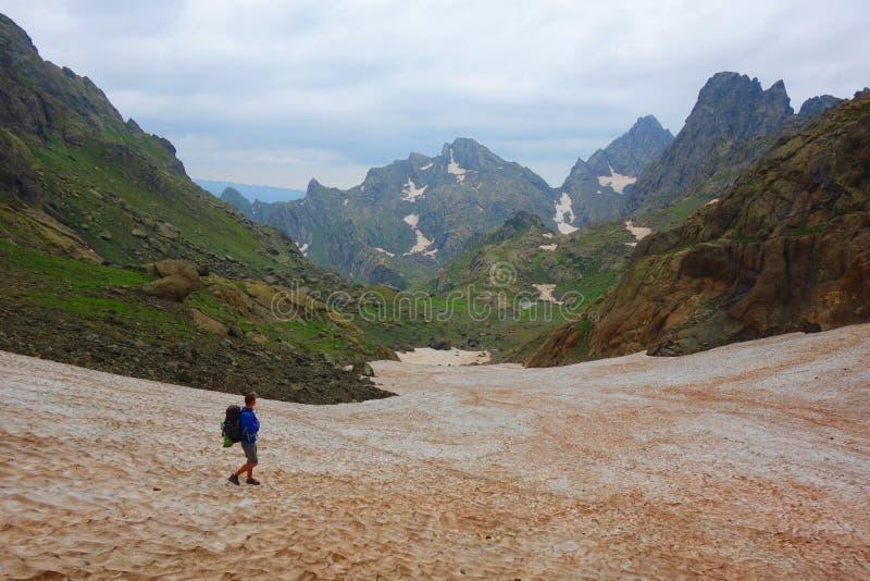与一个年轻人的供徒步旅行的小道在高加索山脉的一个多雪的Tobavarchkhili山口的在变成银色湖的远足的乔治亚 图库摄影