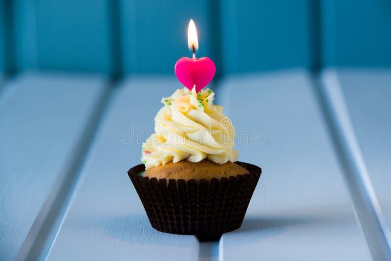 与一个心形的蜡烛的杯形蛋糕1的-第一个生日 库存图片