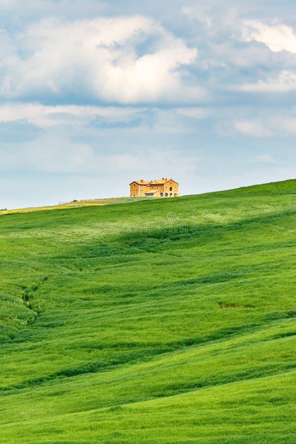 与一个房子的草地小山的 免版税库存图片
