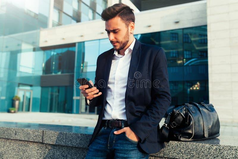 与一个手机的千福年的商人在他的手上 库存图片