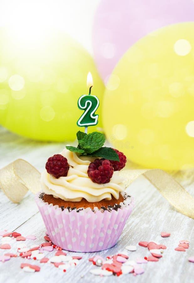 与一个数字两个蜡烛的杯形蛋糕 免版税库存图片