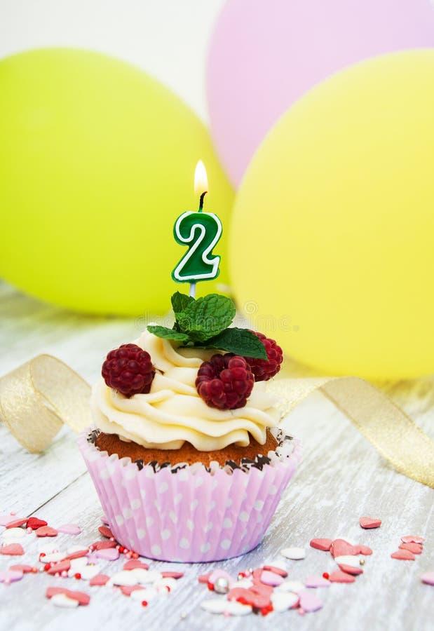 与一个数字两个蜡烛的杯形蛋糕 图库摄影