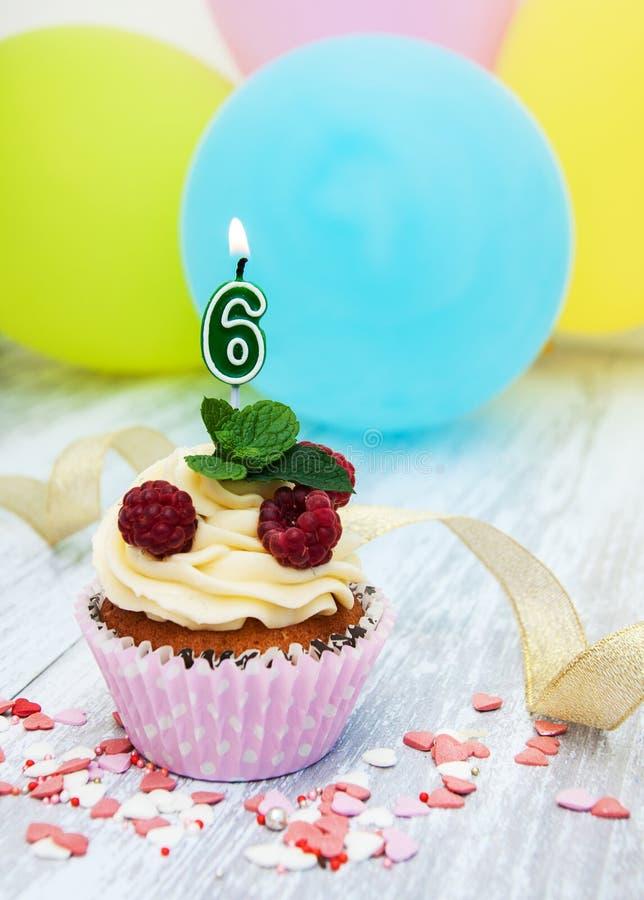 与一个数字六个蜡烛的杯形蛋糕 图库摄影