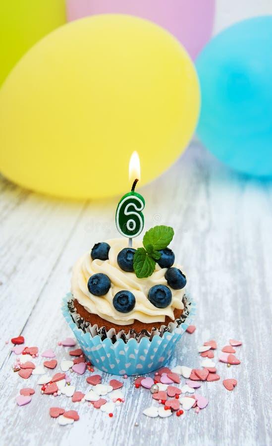 与一个数字六个蜡烛的杯形蛋糕 库存照片