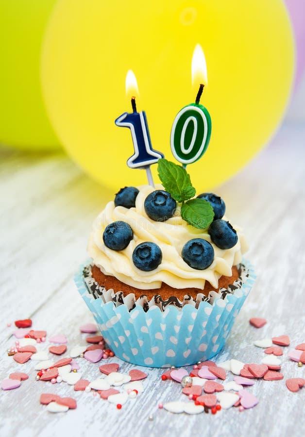 与一个数字十个蜡烛的杯形蛋糕 免版税库存照片