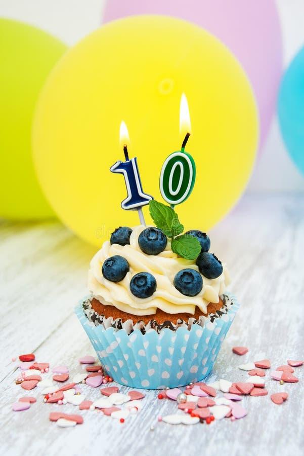 与一个数字十个蜡烛的杯形蛋糕 免版税库存图片