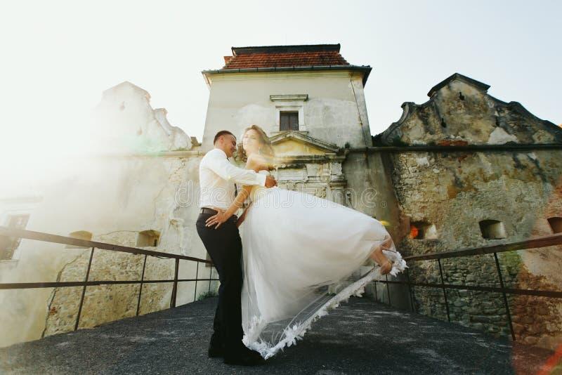 与一个新娘的未婚夫舞蹈在一座老桥梁的阳光下 免版税库存照片