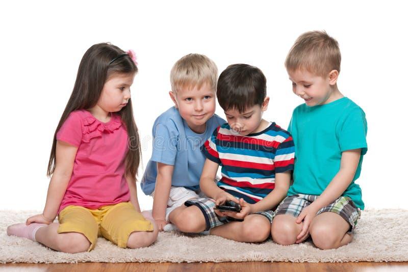 与一个新的小配件的四个孩子 免版税库存照片