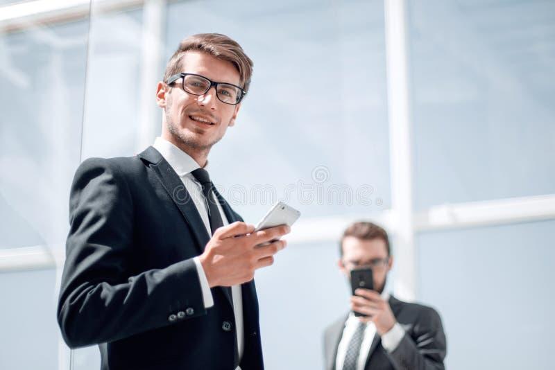 与一个智能手机的现代商人在背景办公室 免版税库存照片