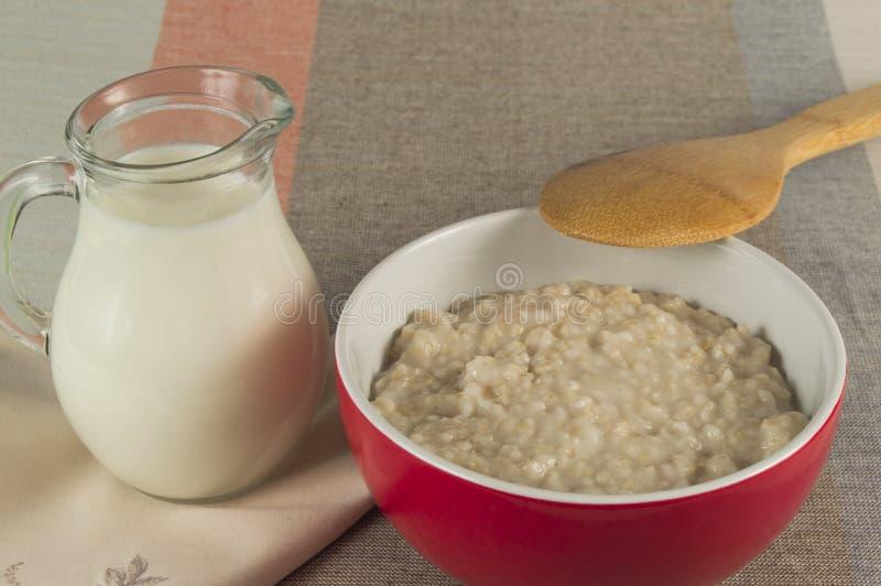 与一个木匙子和水罐的碗粥牛奶 库存图片