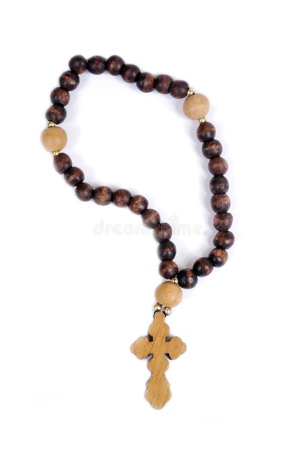 与一个木十字架的教会小珠在白色背景 对读的祷告的教会辅助部件 免版税库存照片