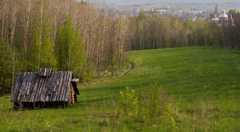 与一个木日志谷仓的农村风景以被弄脏的东正教为背景的前景的 免版税图库摄影