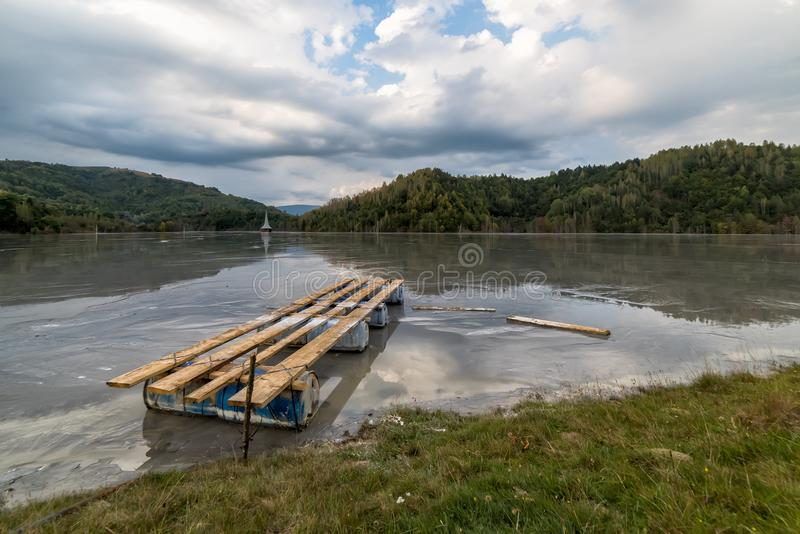 与一个木桥和一个凹下去的教会的美好的风景在含毒物污染了湖由于铜采矿 图库摄影