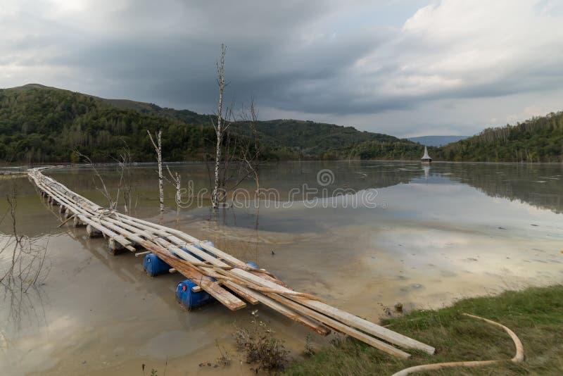 与一个木桥和一个凹下去的教会的美好的风景在含毒物污染了湖由于铜采矿 免版税库存图片