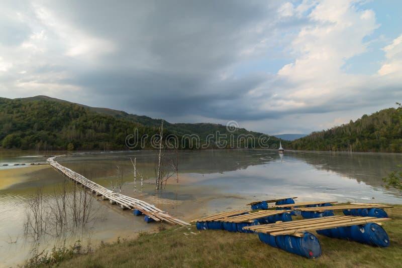 与一个木桥和一个凹下去的教会的美好的风景在含毒物污染了湖由于铜采矿 库存照片