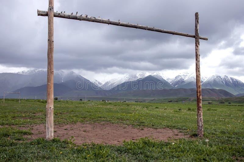 与一个木门的土气领域踢的在一个山土坎的背景的橄榄球与积雪覆盖的峰顶的 图库摄影