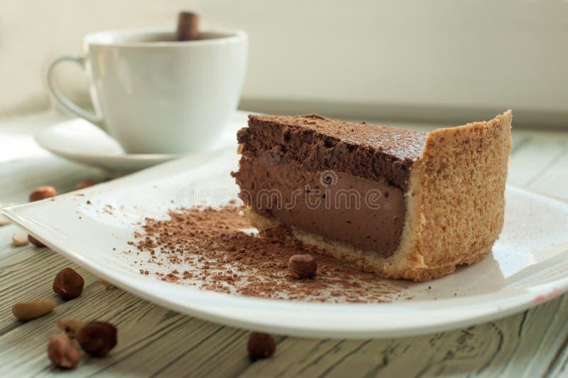 与一个杯子无奶咖啡和用可可粉和坚果装饰的巧克力乳酪蛋糕的和平的构成 免版税库存图片