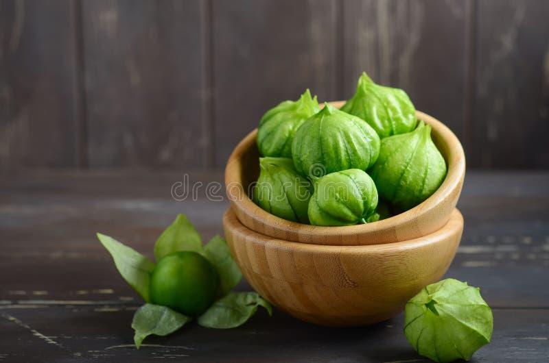与一个果壳的新鲜的有机绿色tomatillos空泡philadelphica在土气木桌上 库存照片