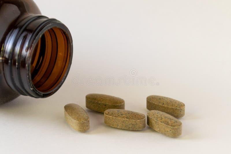 与一个棕色玻璃瓶的每日多种维生素 免版税库存照片