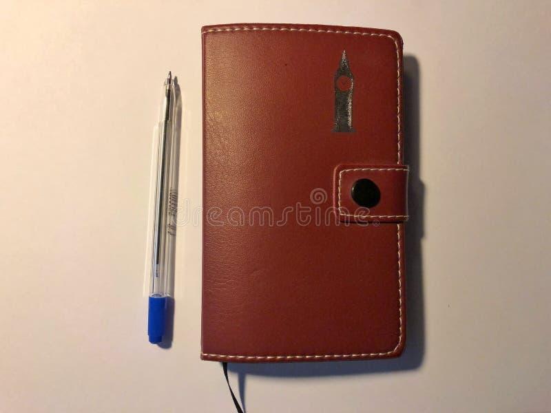 与一个棕色笔记本的蓝色笔在白色背景 库存照片