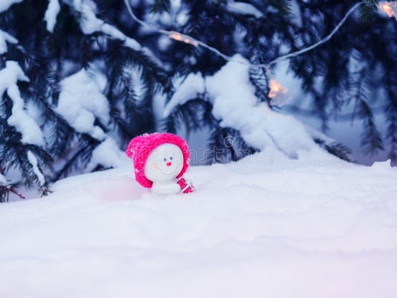 与一个欢乐逗人喜爱的玩具雪人的卡片在坐在与礼物的随风飘飞的雪的一个明亮的桃红色盖帽在圣诞树下 库存照片
