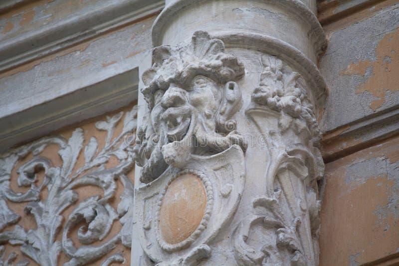 与一个浅浮雕的老专栏以一张恶魔般的面孔的形式 ?? 免版税库存照片