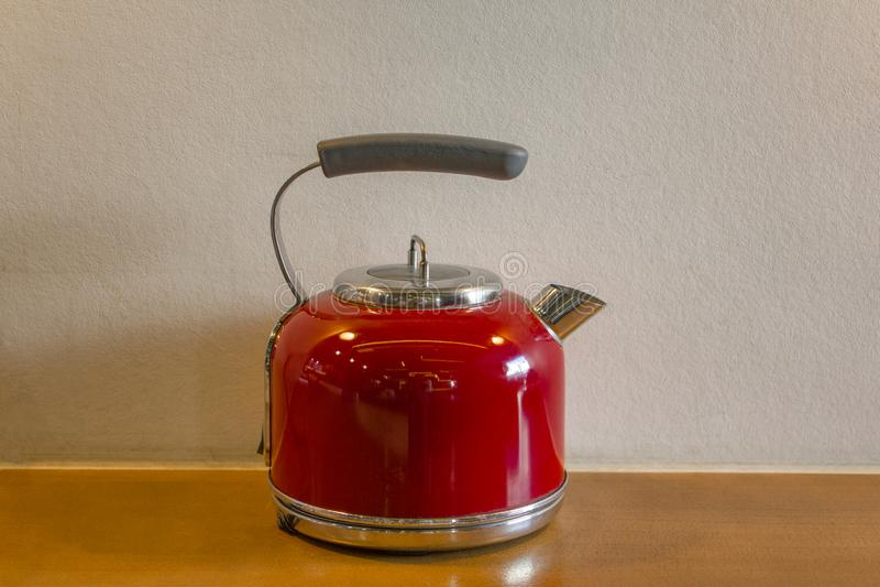 与一个灰色把柄特写镜头的红色电水壶站立桌的黄色木表面上以白色为背景 免版税库存图片