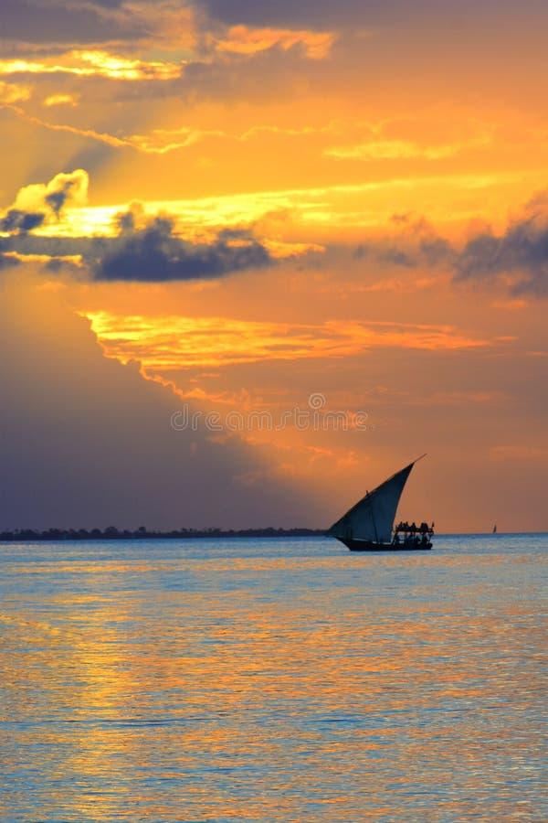 与一个现出轮廓的小船航行的惊人的金黄日落沿它的反对生动的五颜六色的天空的旅途 免版税库存照片