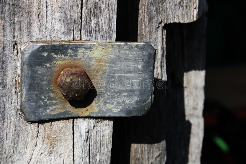 与一个生锈的螺栓的葡萄酒金属元素在灰色木门的背景在一个老被放弃的谷仓 免版税图库摄影