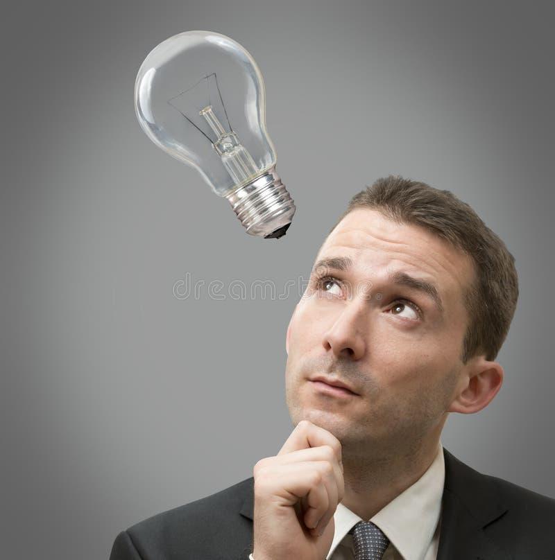 与一个电灯泡的生意人认为的概念 免版税图库摄影