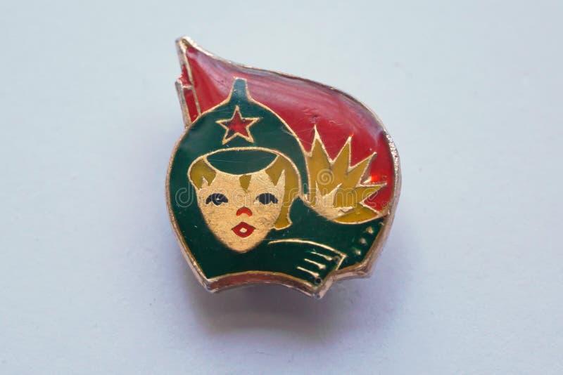 与一个男孩的图象的苏联徽章一个减速火箭的军用帽子的有在红旗的背景的一个五针对性的星的 库存图片