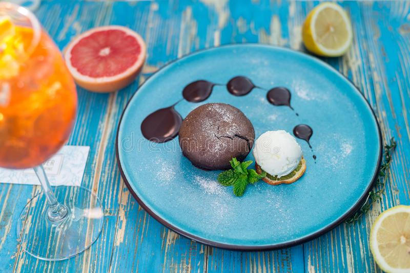与一个白色冰淇凌球的巧克力蛋糕在一块蓝色板材 库存照片