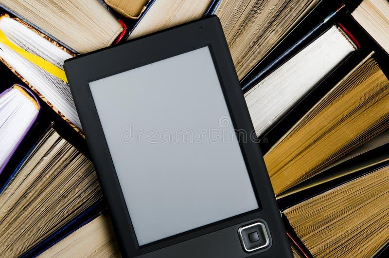 与一个白色屏幕的eBook在说谎在黑暗的背景的开放多彩多姿的书,特写镜头说谎 免版税库存图片