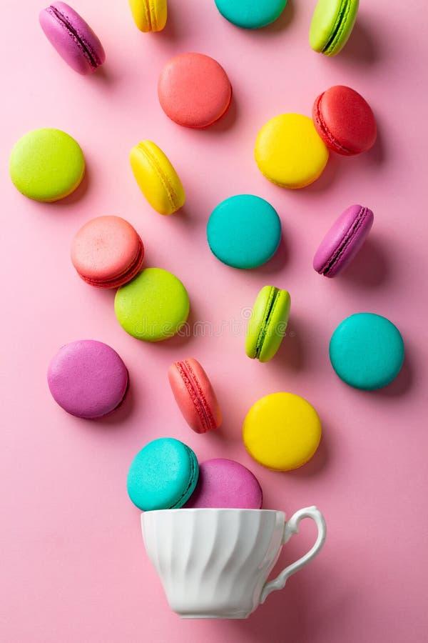 与一个白色杯子的蛋白杏仁饼干点心在桃红色淡色背景 r r 免版税库存照片